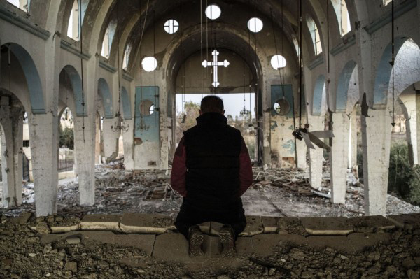 Man praying in a destroyed church